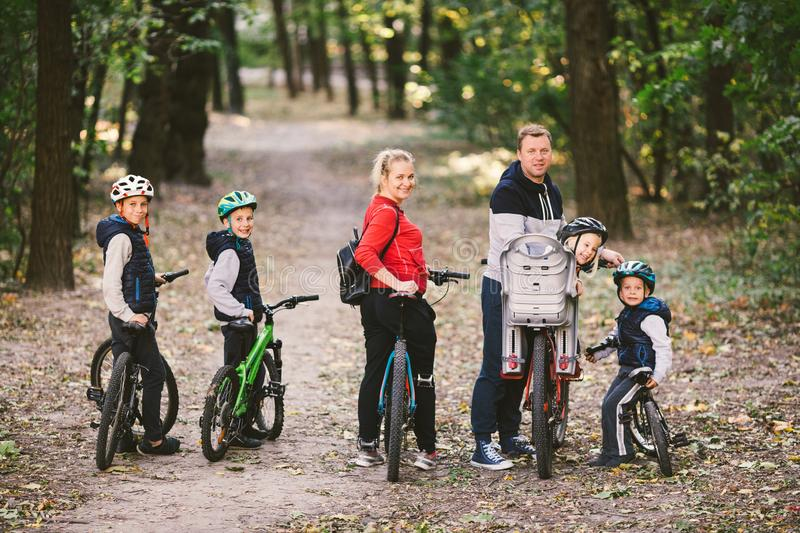 Parents and kids cycling on forest trail. family in warm clothes cycling autumn park. Family mountain bike on forest. active royalty free stock images