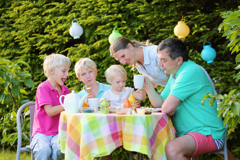 Parents with kids having lunch outdoors. Happy family, parents with three kids, two teenage twin boys and cute toddler girl enjoying lunch with fruits, tea and royalty free stock images