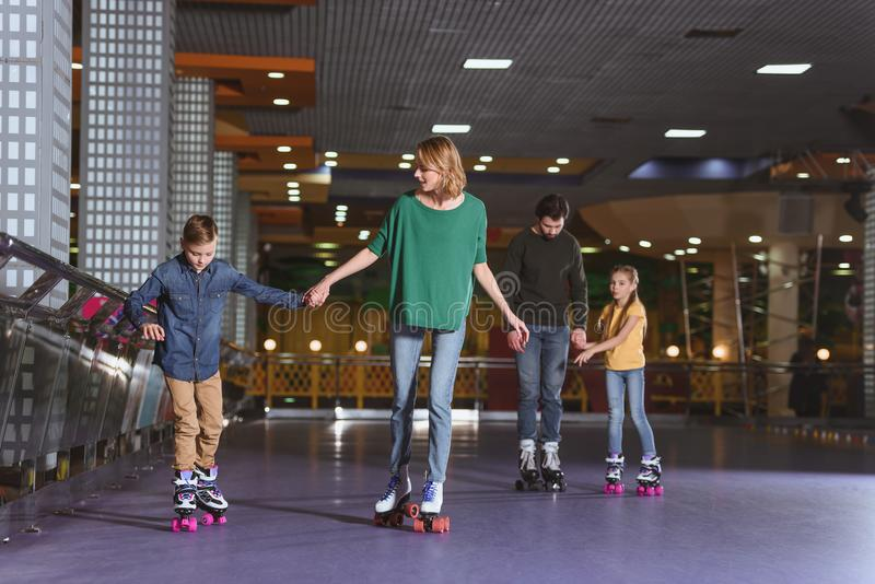 parents and kids skating on roller stock photo