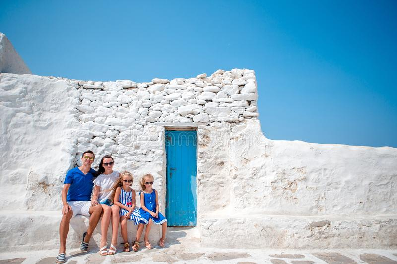 Parents and kids at street of typical greek traditional village on Mykonos Island, in Greece. Family vacation in Europe. Parents and kids at street of typical royalty free stock photography