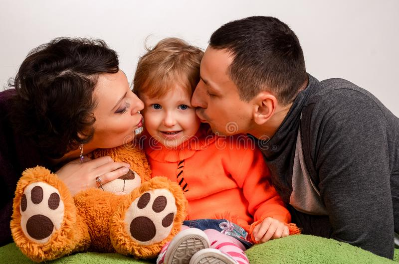 Parents kiss little daughter on a white background stock photo