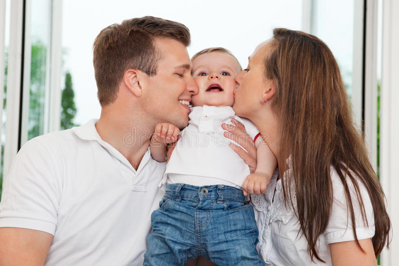 Parents kissing child royalty free stock image