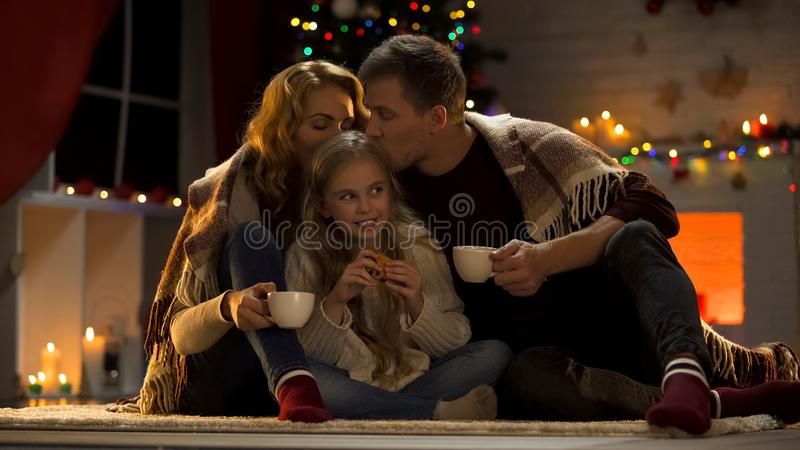 Parents kissing daughter, drinking hot cocoa near Xmas tree, festive atmosphere stock image