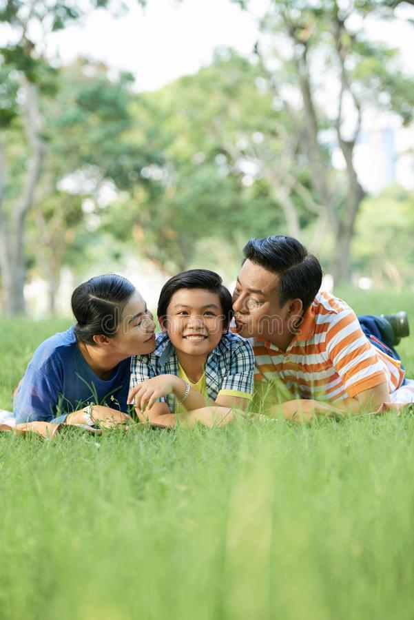 Parents kissing son. Mature Vietnamese husband and wife kissing their son on both cheeks royalty free stock photography