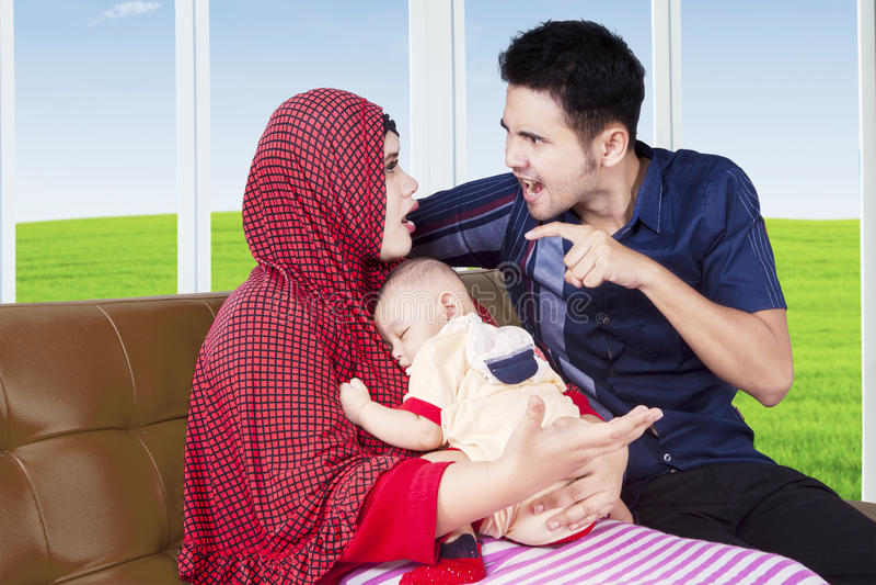 Parents la discusión mientras que lleva a su bebé fotos de archivo
