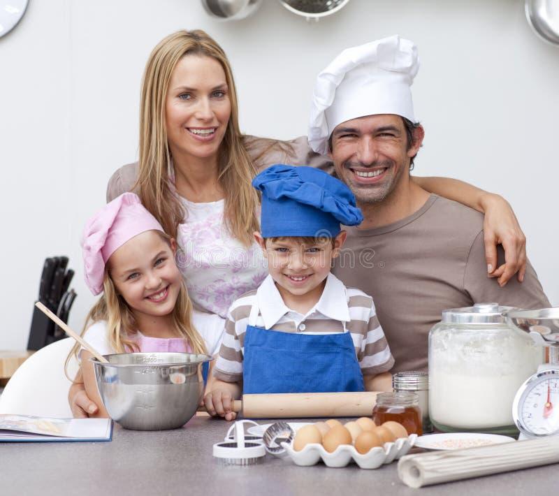 Parents les enfants de aide faisant cuire au four dans la cuisine photographie stock libre de droits