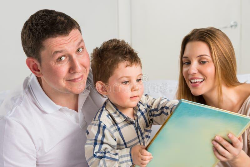 Parents lisant l'histoire avec le fils photos stock
