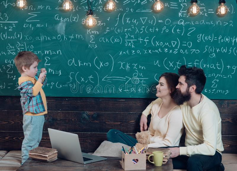 Parents listening their son, classroom, laptop, chalkboard on background. Homeschooling concept. Parents teaching kid at stock images
