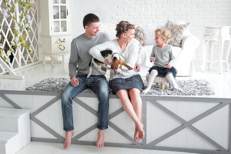 Parents and little girl playing with a dog royalty free stock photos