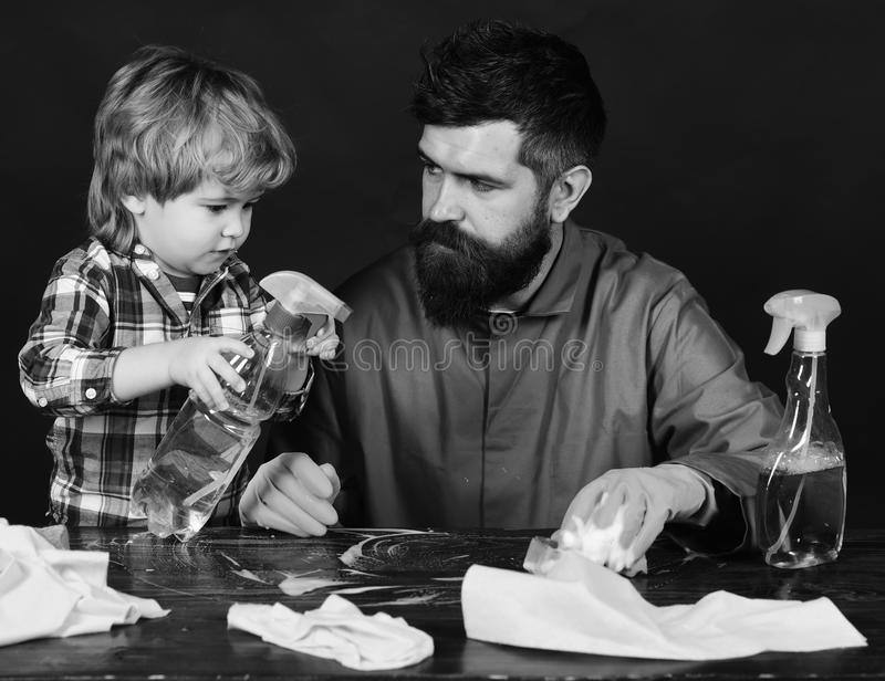 Parents little helper concept. Guy with beard in rubber gloves at table with cleaning supplies on. Man with cute child stock images