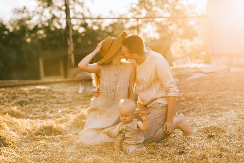parents with little son in linen clothing near by kissing while resting on hay royalty free stock images