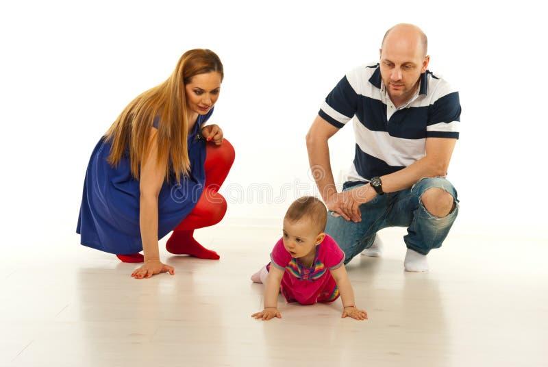 Parents looking at baby crawling