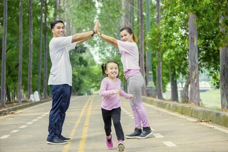 Parents making house symbol with their child. Young parents playing with their daughter while making house symbol in the park royalty free stock photos