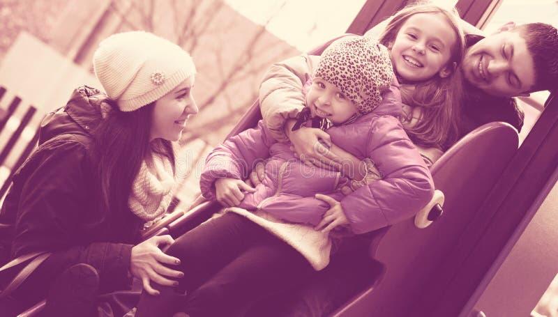 Parents a niños de ayuda en diapositiva fotos de archivo libres de regalías