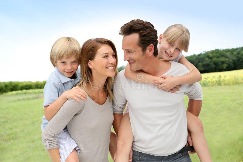 Parents a niños que llevan en su sonrisa trasera fotografía de archivo libre de regalías