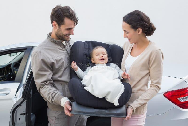Parents o bebê levando em seu banco de carro imagens de stock royalty free