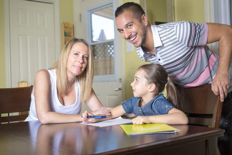 Parents o filho de ajuda com trabalhos de casa no interior home imagens de stock royalty free