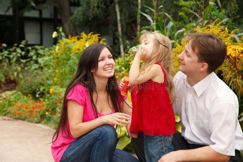 Parents observe as daughter blows soap bubbles