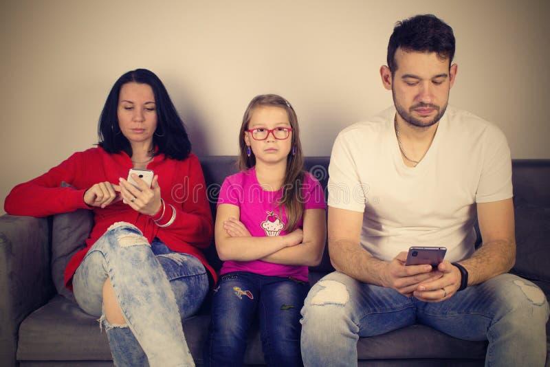 Parents occupés avec les téléphones portables et la petite fille fâchée image stock