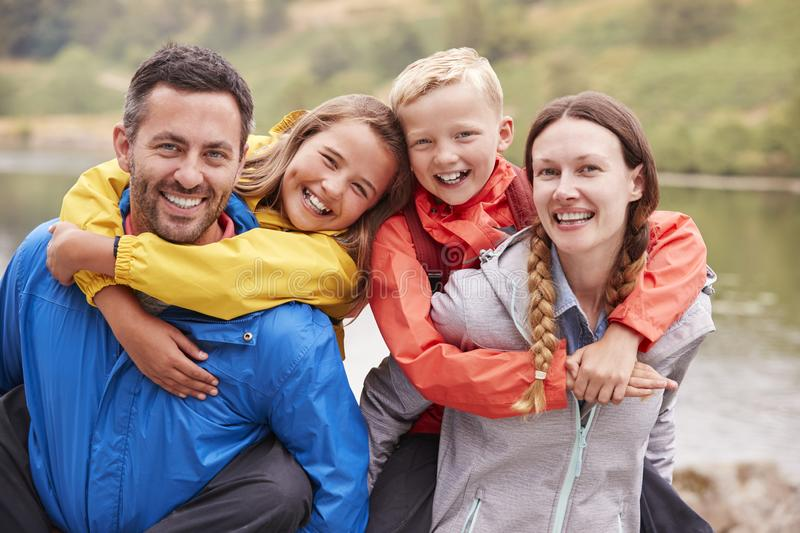 Parents piggybacking their children and laughing to camera in the countryside, close up, Lake District, UK royalty free stock image