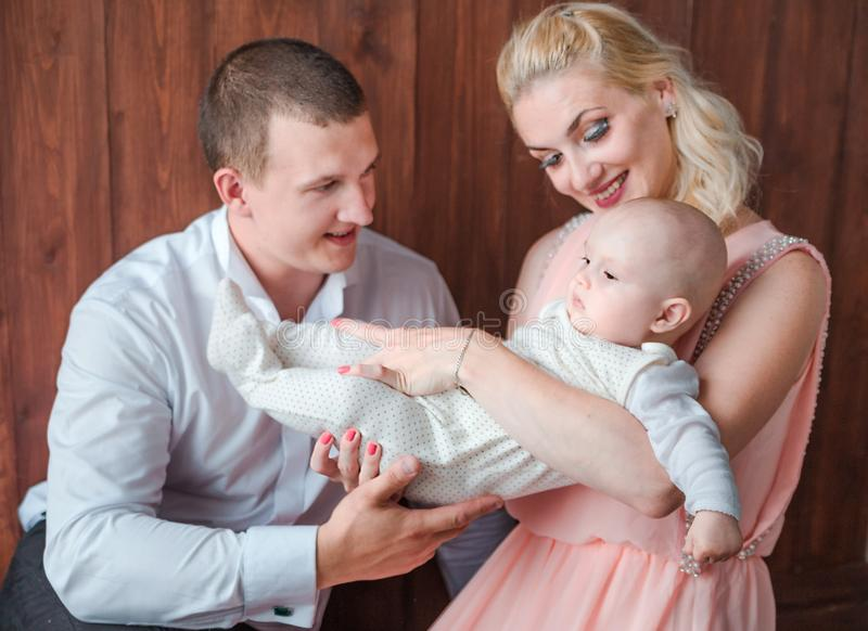 Parents play with their young son on a wooden background. Photo of parents play with their young son on a wooden background royalty free stock photos