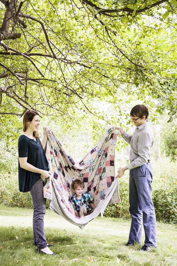 Parents playing with child in blanket. Smiling parents swinging happy boy in patchwork quilt outside royalty free stock images