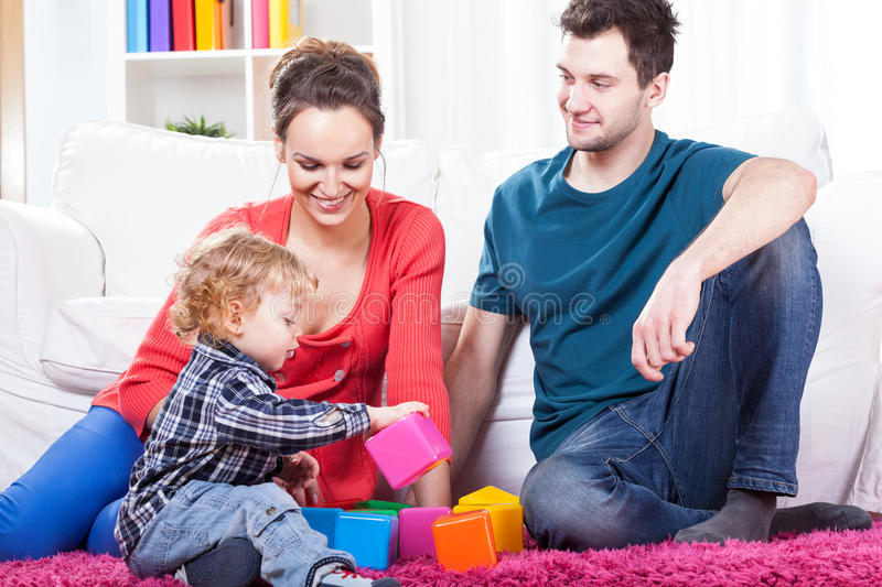 Parents playing with child. Young parents playing with their child in living room