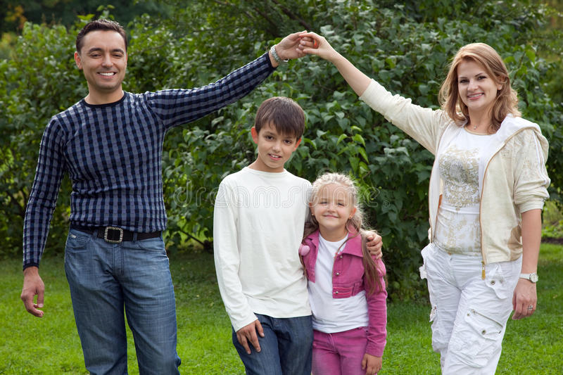 Parents playing with children in park stock photography