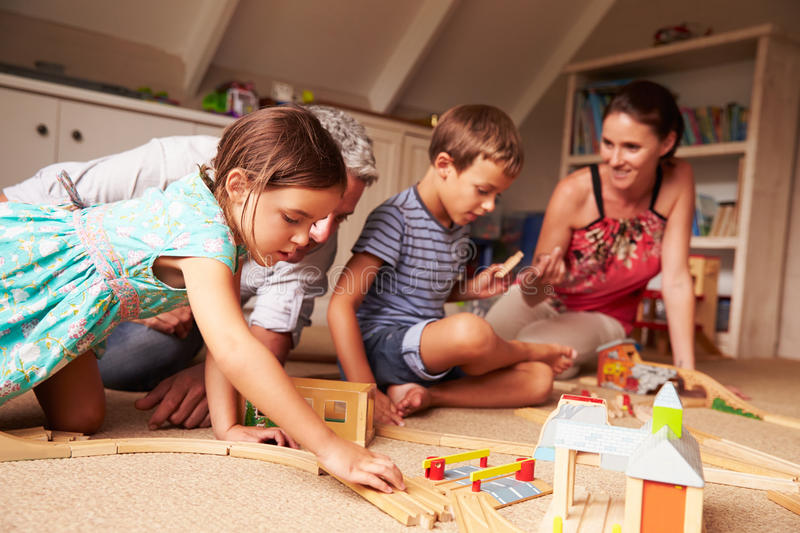 Parents playing with kids and toys in an attic playroom stock image
