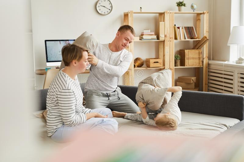 Parents playing pillow fight with son stock image