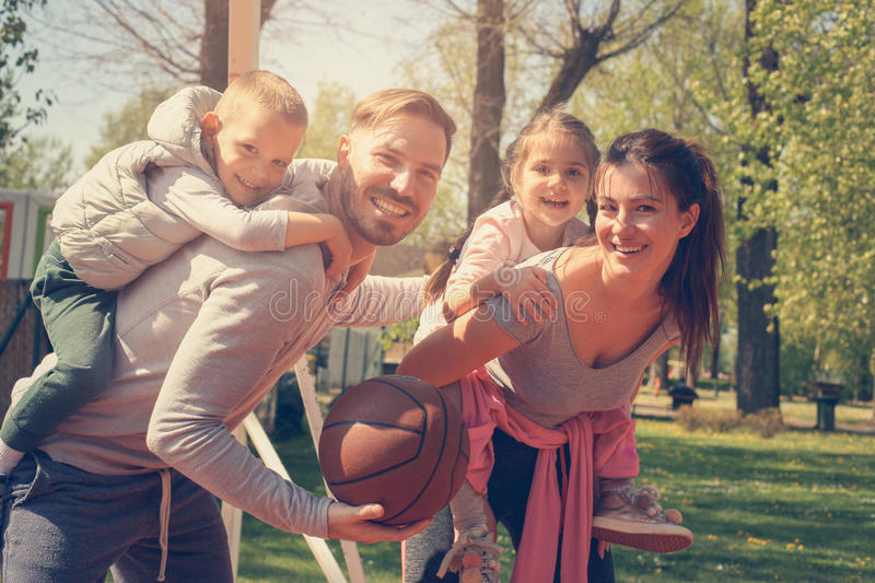 Parents playing with their children in the park with basket ball. stock images