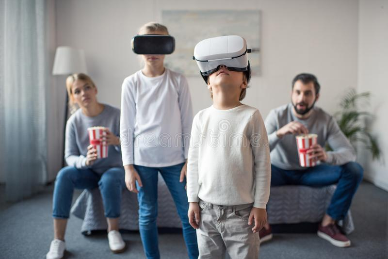 Parents with pop corn watching kids playing in vr headsets. At home stock photos