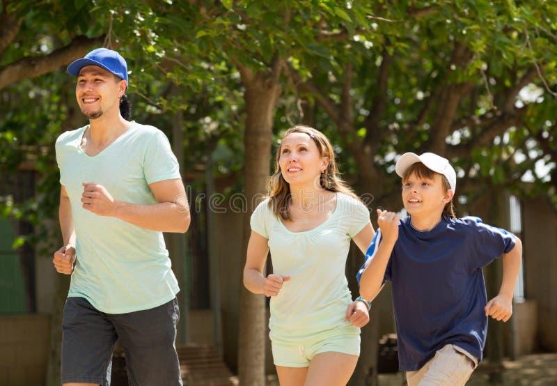 Parents positifs avec le fils courant en parc photographie stock libre de droits