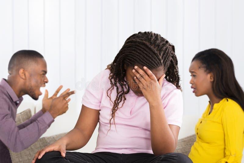 Parents se disputant derri?re la fille boulevers?e photos libres de droits