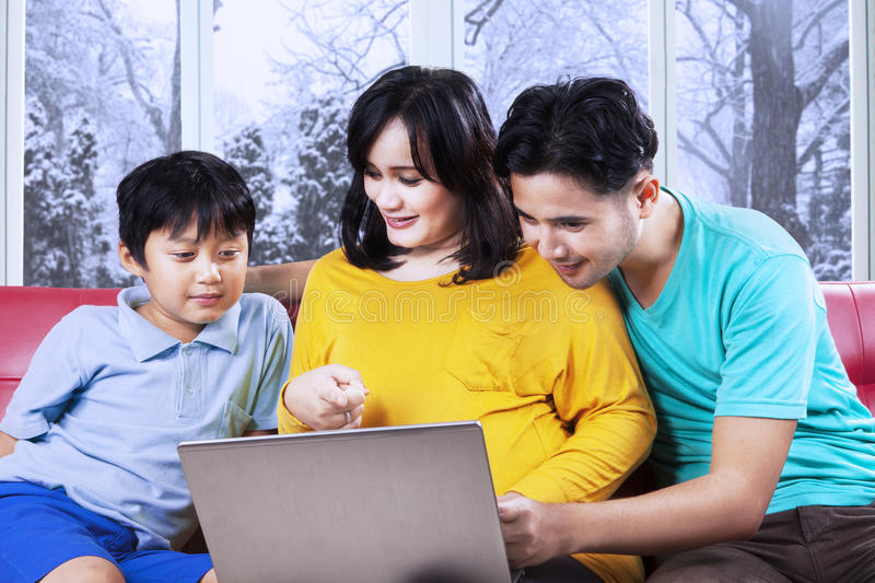 Parents showing laptop to their son. Portrait of two parents showing a laptop screen to their son on sofa at home in winter day stock photography