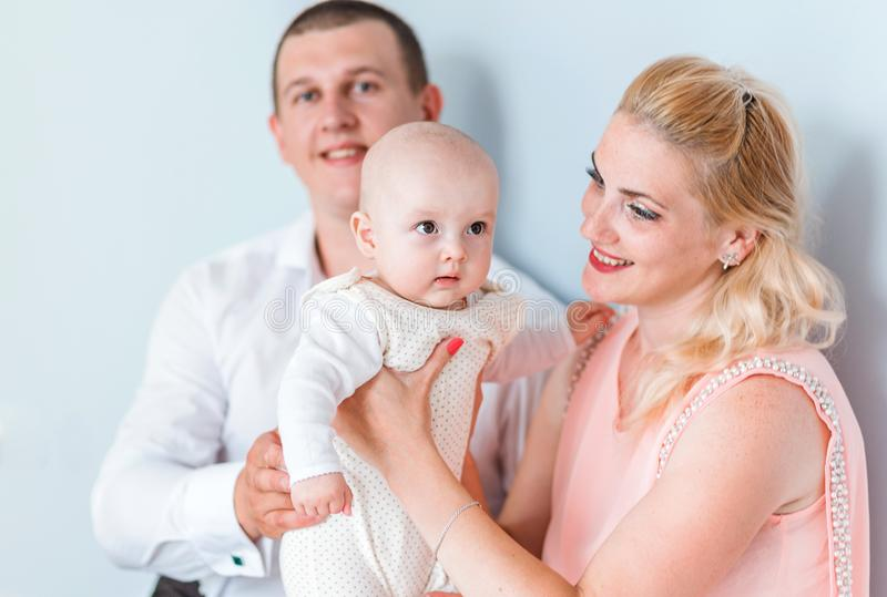Parents with a small child are posing against the blue wall. Photo of Parents with a small child are posing against the blue wall royalty free stock photo