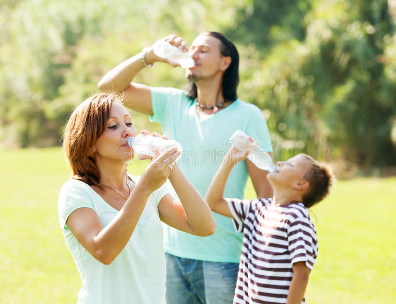 Parents with son drinking from bottles royalty free stock photos
