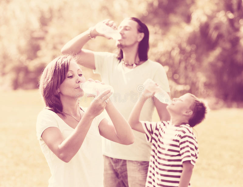 Parents with son drinking from bottles royalty free stock photography