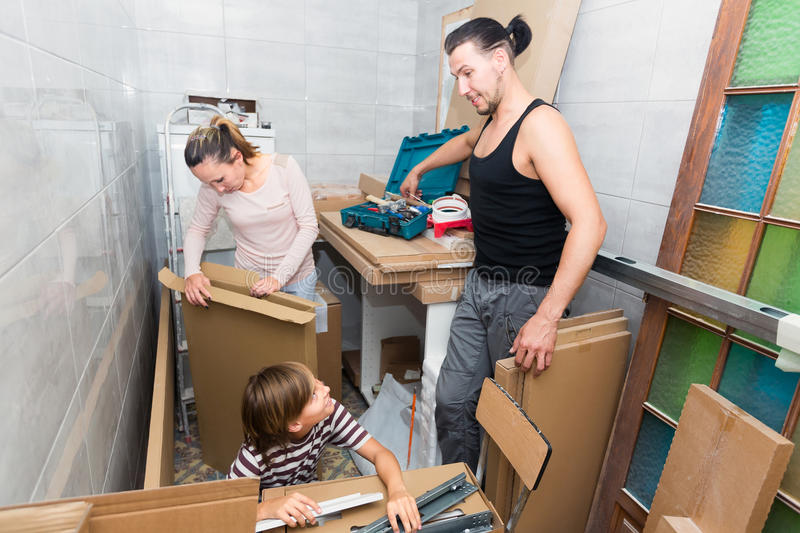 Parents with son unpacking boxes. Happy parents with their son in the new apartment unpacking boxes stock photography