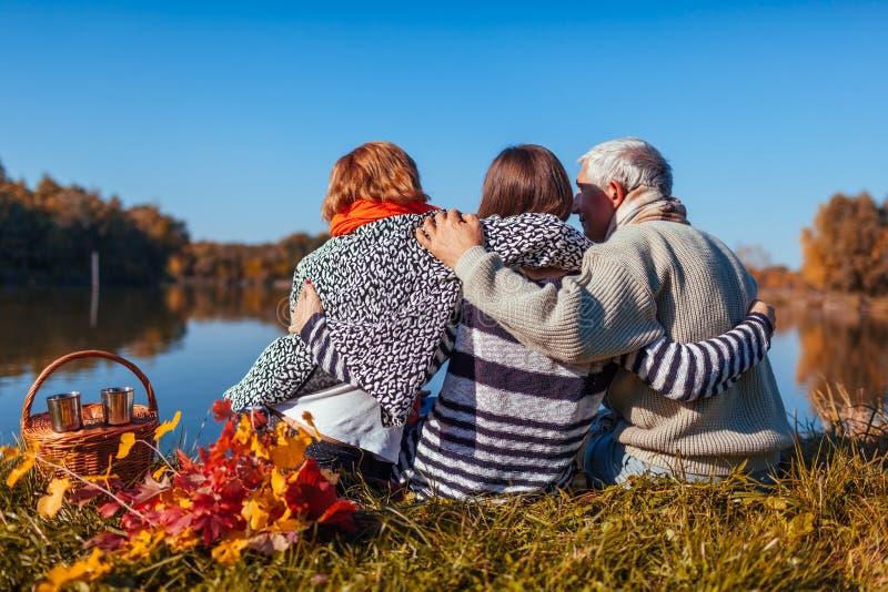 Parents supérieurs détendant par le lac d'automne avec leur fille adulte Valeurs familiales Les gens ayant le pique-nique photos stock