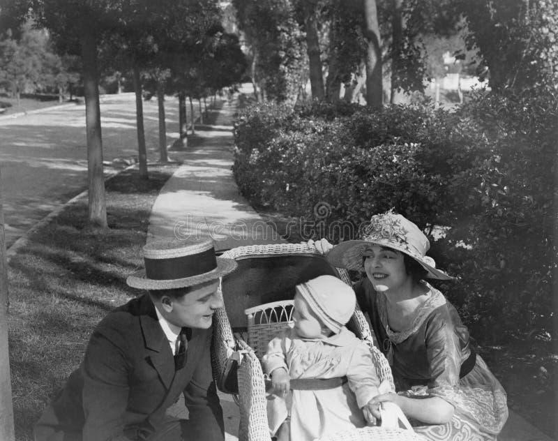 Parents sur la promenade avec le bébé (toutes les personnes représentées ne sont pas plus long vivantes et aucun domaine n'existe photos libres de droits