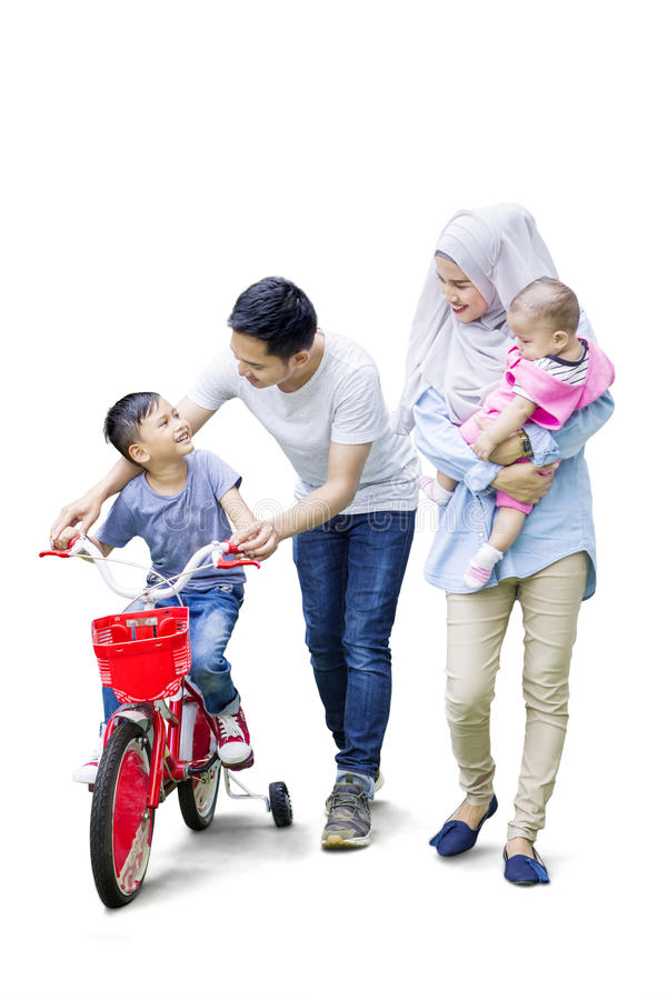 Parents teach their son to ride bicycle royalty free stock images