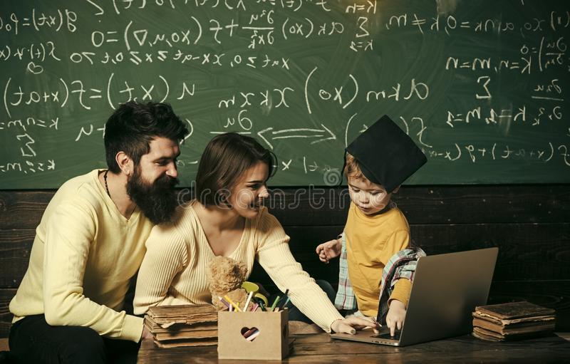 Parents teaches son, chalkboard on background. Modern education concept. Smart child in graduate cap likes to study. Parents teaching kid to use laptop. Boy stock photography