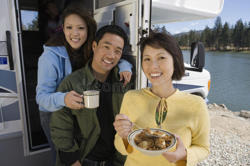 Parents and teenage daughter eating breakfast in RV at lake royalty free stock images