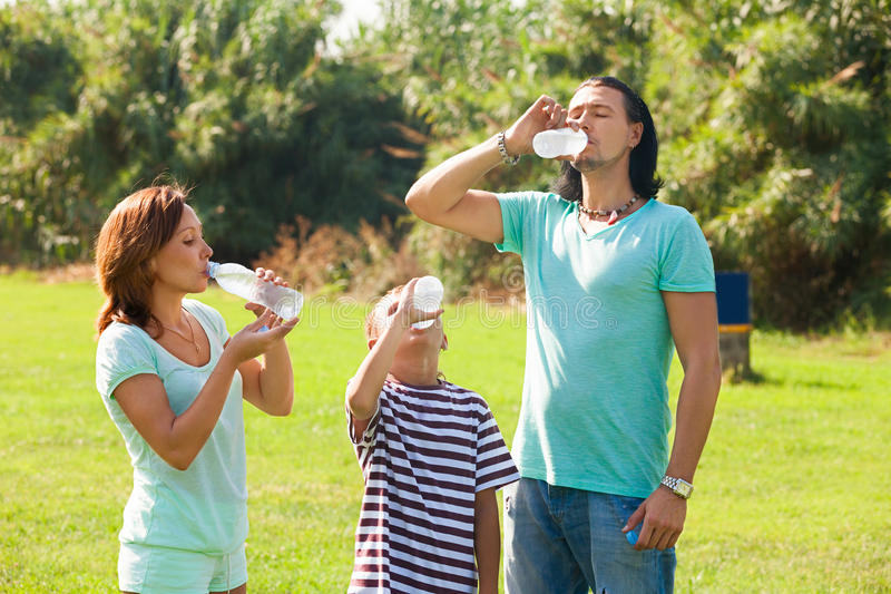 Parents with teenager drinking from bottles stock photography