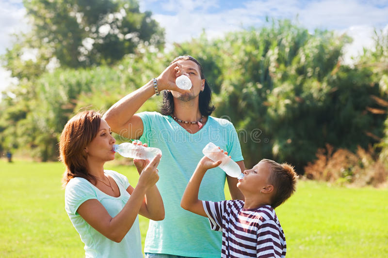 Parents with teenager drinking cold water. From plastic bottles in summer park stock image