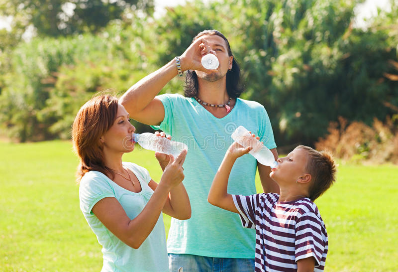 Parents with teenager drinking water stock image