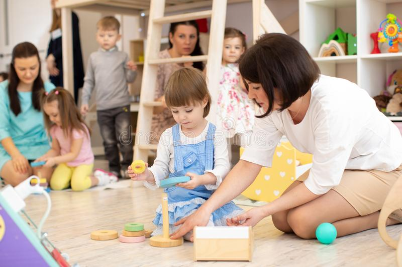 Parents with children playing in playroom in daycare. Parents with their children playing in playroom in daycare royalty free stock photography