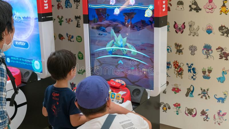 Parents with their children playing Pokemon branded arcade video games at Pokemon Center, Tokyo, Japan stock images