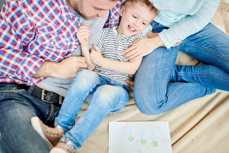 Parents Tickling Cute Little Boy stock photo